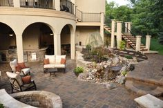 Private Residence, Shawnee, Kansas 2011 HNA Hardscape Project Award Winner Contractor: Ideal Lawn & Landscape  This outdoor room expands a covered deck to create a secluded space for relaxation and entertaining. The homeowner desired a kitchen with ample countertop space, a bar for evening or breakfast seating, a patio built around a flowing water feature, and a fire pit. A four-piece concrete paver path meets the transition and follows a stream and waterfall to the lower patio. Outdoor Living Areas, Outdoor Rooms, Outdoor Decor, Shawnee Kansas, Paver Path, Lawn And Landscape, Concrete Pavers, Unique Lighting, Award Winner