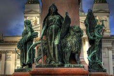 The Finnish Maiden and the Finnish Lion in the monument of Alexander II of Russia (Walter Runeberg) at the Senate Square in Helsinki. - Walter Runebergin työt olivat aluksi ihanteellis-klassisia,myöhemm.hänen töihinsä tuli myös realistisia piirteitä.Hänen töitään ovat mm.Aleksanteri II:n patsas Senaatintorilla,J.L.Runebergin patsas H:gin Esplanadin puistossa sekä Pietari Brahen patsas Raahessa ja Turun Brahenpuistossa (molemmat 1888). Photo: BKfi