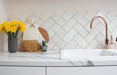 Kitchen Inspiration - copper tap, pastel herringbone tiles and wonderful vignettes made up of marble and wood chopping boards and daffodils.