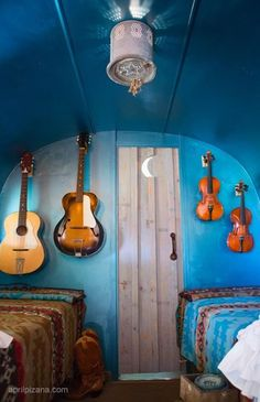 blue paint wall hanging guitar and biola bedroom decor