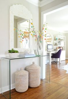 Easter Egg tree in foyer with acrylic console table and inlay mirror with decorative baskets underneath
