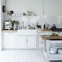 White fronts, black handles, white floor, while metro tile with dark grout, wooden butcher block cover,