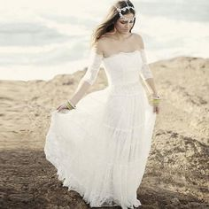 Soft and sweet, this hippie style wedding gown has a strapless, sweetheart neckline and layers of soft lace. The three-quarter cap sleeves are also made of lace. This romantic creation flows into a fl