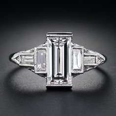 Extra slender emerald-cut diamond, is perfectly suited for this streamlined, geometric, Art Deco style ring, finely crafted in platinum. The bright-white and shining diamond is embraced on both sides by baguette diamond 'T's, which, in turn, are supported by a sparkling diamond side gallery.