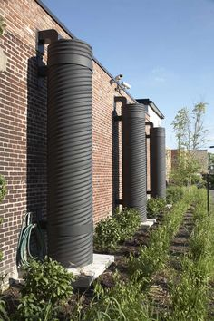 The Green Building | Louisville, KY | FER Studio |  THE GREEN BUILDING is the first commercial building in Louisville to pursue an anticipated LEED Platinum certification. Three massive rain barrels alongside the exterior wall capture any overflow from the green roof above. These pour into an underground culvert which then takes any excess run-off into a rain garden. Excess run-off is also used to irrigate the green roof and a vertical garden, which is used to grow herbs + food for the cafe.
