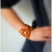 Oi meninas,  olha que linda essa pulseira de laço!!!  Além de linda e super atual ela é muito fácil de fazer. Você vai precisar de um pedaço de couro de uns 10cm por 22cm, tesoura, linha, cola de couro (também pode ser super bonder) e um botão de pressão.  1. Corte o pedaço de couro ...