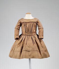 This dress follows the style of women's dresses of the 1840s, which had a V-shaped gathering on the front and a relatively low waist. The garment is beautifully made out of high quality silk with considerable detailing, including a faux oversleeve and undersleeve. The piping at the edges creates an interesting stylistic effect. The dress is in its original form without any apparent changes.