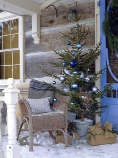 This Log House Porch has all it needs to be a wonderful Christmas display... a simple tree and burlap wrapped gifts lend to a perfect setting!