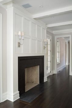 Chic living room boasts a wainscot trim illuminated by TT Double Sconces over a sleek black fireplace accented with a herringbone firebox.