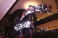 Título de la obra: Waves. Autor: Daniel Canogar. Se trata de una instalación consistente u en una video-escultura hecha con LED y suspendida en el atrium de un edificio de oficinas en Houston. El video muestra gente anónima a la que se grabó arrastrándose por una cinta. URL del artista: http://www.danielcanogar.com/index.php?lang=es Video en youtube: https://www.youtube.com/watch?v=TyBJyv0fvrw