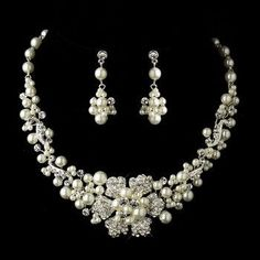 This delightful choker-style bridal necklace and earring set features clusters of luminous ivory faux pearls and dazzling clear crystals with a charming silver plated flower in the center that is ador