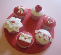Super pretty cupcake concept for Valentines Day (no recipe or instructions). I'm always amazed at some cupcake pictures that look too perfect to be read. I can't imagine how to get these perfect cupcake tops. I'm guessing these are cookie tops or baked using a round pan and placed on top. Either way, these are frosted and decorated with fondant. You can see there is also use of edible food glitter on the red rose.