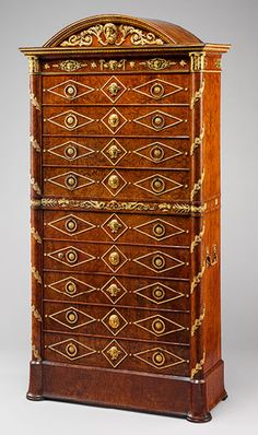 Desk (secrétaire), ca. 1804–15 French Amboyna on pine with gilt-bronze mounts Tradition has it that this secretary was presented by Napoleon to Maréchal Lannes, duc de Montebello (1769–1809). Although the handles and mounts are arranged to give the illusion of a chest of drawers, the upper part is a fall front that conceals a writing compartment.