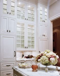 Featured in Gentry Magazine: Love the tall cabinets, white marble, white cabinets, hardware, backsplash...