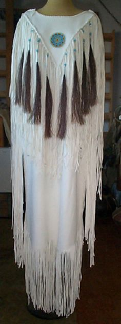 White hides, suede side out, deer/elk hide dress, beaded rosette, horse hair tassels, glass beads, tin cones and bone hairpipe, all done by hand.
