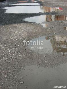 Eine alte Fabrik spiegelt sich im Wasser einer Pfütze auf einem Schotterparkplatz in Münster in Westfalen