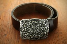 Western style rectangular belt buckle with scroll-work design and a floral pattern.