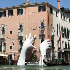 Deux mains colossales engloutissent Venise pour sensibiliser au réchauffement climatique.   Pour alerter sur la montée des eaux, l'artiste italien Lorenzo Quinn a érigé une sculpture représentant deux mains s'agrippant à un bâtiment historique de la cité italienne.