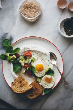 Tomato Cucumber Salad with Fried Eggs by @yehmolly | Savory yogurt with a pinch of za'atar makes for a perfect breakfast