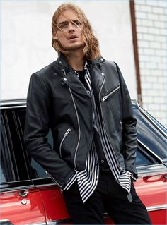 Dutch model Ton Heukels wears a leather jacket with a striped shirt and jeans.