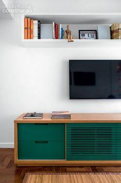 o aparador exibe acabamento de laca verde. mesmo fechada, a porta central, ripada, mantém ventilados os equipamentos de TV