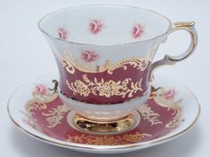 Paragon tea cup and saucer. Made in England  Pembroke J pattern. Red and white ground with a gold design and pink roses on the cup and saucer.