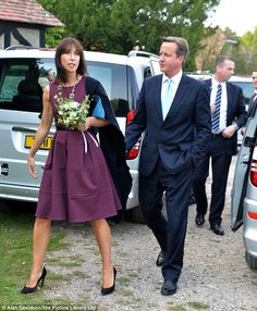 The Camerons attended the high society wedding in Hampshire - with Samantha Cameron wearing a purple, knee-length dress, black high-heeled shoes and carrying a blue clutch bag