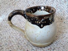 "By Shelley Duncan. Stoneware mug glazed in Cone 6 ""Harvest Gold"" with rim dipped in Temmoku"""