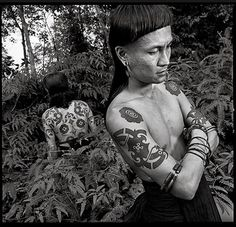 "For the Dyak people of Borneo, tattoos once commemorated headhunting expeditions. The markings on some modern Dyaks, on the left is Ernesto Kalum, represent ""a modern interpretation of traditional headhunting tattoos,"" says photographer Chris Rainier."