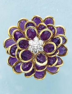 An Amethyst and Diamond 'Flower' Ring  Of flowerhead design, centering upon a circular-cut diamond cluster pistil, extending an overlapping series of flexible amethyst petals, to the plain hoop, mounted in 18K yellow gold.