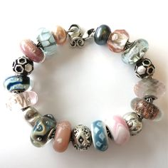 """CLOCKWISE FROM CLASP: """"LIMITED EDITION PEACOCK PEARL"""", """"PINK PRISM"""", """"SILVER MOUNTAIN"""", """"BEE ON HIVE"""" (RETIRED), """"ROSE QUARTZ"""", """"BLUE DESERT"""", """"SPARROW"""" (RETIRED), """"CUSTOM BEAD BY GEORGINA OF TROLLBEADS CANADA"""", """"LIMITED EDITION KIMONO BEAD"""", """"""""ZANZIBAR""""(RETIRED), """"LIMITED EDITION KIMONO BEAD"""", """"AZURE BUBBLES"""", """"HEART"""", """"UNIQUE"""", """"UNIQUE"""", """"BEE ON HIVE"""" (RETIRED), """"PINK DESERT"""", """"PALE BLUE SHADOW"""", """"ROSA PEARL"""""""