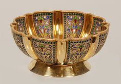 A Russian silver gilt and plique-a-jour enamel bowl, Ivan Khlebnikov, Moscow, 1908-1917. The scalloped circular bowl on a flaring circular base decorated in raised panels of stylized multi-color floral motifs surrounded by a border of translucent blue enamel beads alternating with raised gilt ribbing.