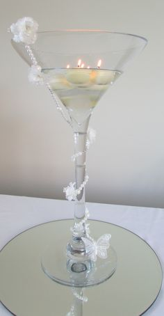 Tall Martini vase with floating candles and stem decorated with pearls and white flowers