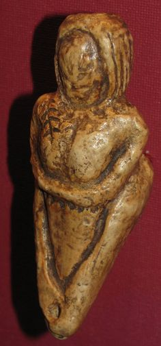 'The Mal'ta Venus Figurine'  --  Circa 20,000-23,000 BCE  --  Excavted from Mal'ta (Siberia)  --  The figure appears to be wearing a fur hood.  Below her folded arms, there appears to be a belt consisting of linked disks. Belonging to the Austrian Natural History Museum, Vienna  --  Photo Credit: Don Hitchcock, 2008.
