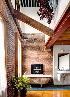 Now this is what we call a bath: A lovely clawfoot tub, exposed brick for days, plus some wooden beams for good measure.