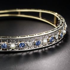 Sapphire and Natural Pearl Bangle Bracelet. From the early 20th century, blue sapphires, old European-cut diamonds and natural seed pearls harmonize in a row of delicate flowers. Made in platinum over 18 karat gold, this hinged bangle adds a bit of brightness to any day. American-made by The Hagerstom Co. in Newark, NJ.