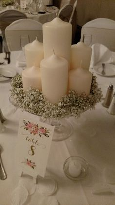 Wedding reception centerpiece with pillar candles surrounded by baby's breath on a cake stand.