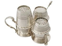 By George Fox 1864 The pieces of this impressive antique Victorian sterling silver cruet set have a barrel shaped form. This very fine, collectable cruet set comprises of two powder pots, a mustard pot and the original hallmarked mustard spoon. Each piece is ornamented with bands of thread decoration. Both powder pots retain the original hallmarked push fit covers embellished with pierced decoration. The mustard pot is fitted with a hallmarked hinged cover.