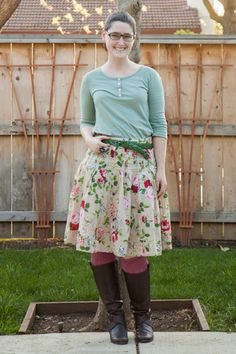 Green 3/4 sleeve top, floral skirt, green braided belt, pink OTK socks, brown boots.