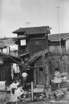Japanese family candid outside ramshackle house. Marc Riboud, Japan 1959