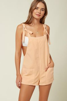 This is an overall-style romper that has a soft cotton design and front hand pockets. O'Neill Women's woven tank romper Inseam Overall style with tie straps Hand pockets Stitching detail Metal logo badge Cotton, Linen