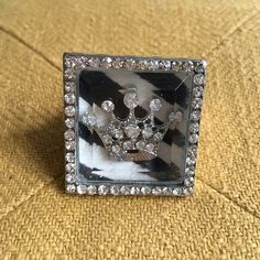 Black & White Cowhide & Crystal Crown Ring This statement ring features a black & white cowhide background with a rhinestone crown in the forefront--all in a cute rhinestone bordered glass picture frame. Stretchy back makes it suitable for all ring sizes. Jewelry Rings