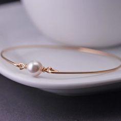 An 8mm white Swarovski pearl is the center of this bangle bracelet. Each bangle is made of heavy gauge, 14k gold filled wire, hand-hammered and tumbled for shine and strength. The high-quality materials and detailed process create a superior, heirloom-quality product to be treasured for a lifetime. *There is an option to add a personalized initial charm as shown in the first picture, or add more initial charms. If you select this option, please let me know the letter (or letters) you want in…