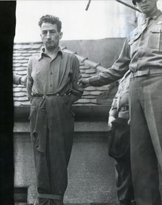 SS Haupscharfuehrer Hans Spatzenegger, director of the Mauthausen quarries, approaches the gallows at Landsberg prison. The soldier behind him holds the black hood which will cover his head before he is hanged.