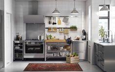 ステンレススチール製の普通サイズのキッチンにホワイトのワークトップとステンレス製の取っ手。ステンレス製のレンジフードとコンロ。