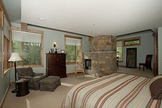 The master suite has a fireplace of hand chiseled natural stone and plenty of windows giving lots of light.