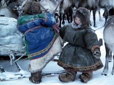 Nenets children getting on a reindeer sledge in the tundra 100km to the north of Yar-Sale, Yamal Peninsula, Arctic Siberia