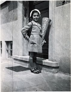 Margot on her first day of school in Frankfurt am Main in 1932. In keeping with German tradition, her parents have given her a big bag of sweets.