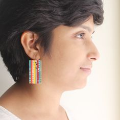 This eco friendly pair of earrings is made entirely out of recycled materials – newspaper and cardboard. The earring base is hand sculpted from recycled cardboard, and sanded to perfection. Thin strips of glossy newspaper, carefully chosen in vibrant shades of red, yellow, blue and green, are then neatly stuck to the sturdy base. The dangles are then given a coat of eco friendly sealant to make it sweat and splash proof. The rectangular dangles hang from hand formed sterling silver ear wires. Lesbian Gifts, Gifts For Bookworms, Literary Gifts, Paper Jewelry, Shades Of Red, Recycled Materials, Newspaper, Handcrafted Jewelry, Sculpting