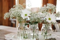 More centerpiece inspiration, possibly dyed/tinted pink flowers in a blue mason jar tied with white ribbon. And home grown or picked flowers to be cost effective!